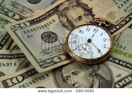 Time And Money concept image. Very clear pocketwatch atop US currency.
