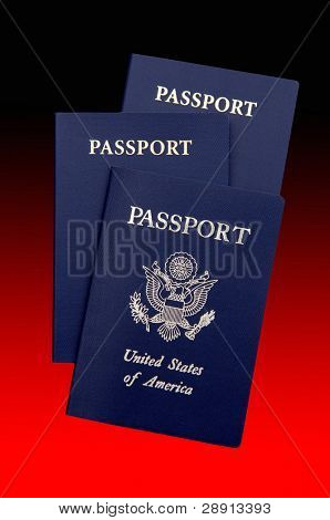 United States passports over a deep black red gradient background.