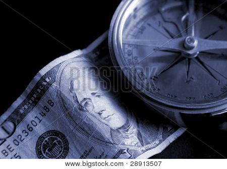 Compass and currency over black - financial navigation concept image.