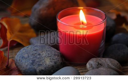 Spa Candle with flat river rocks and autumn leaves