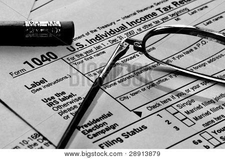 Time to pay the taxes - a black and white image of glasses, pencil and US 1040 tax form.
