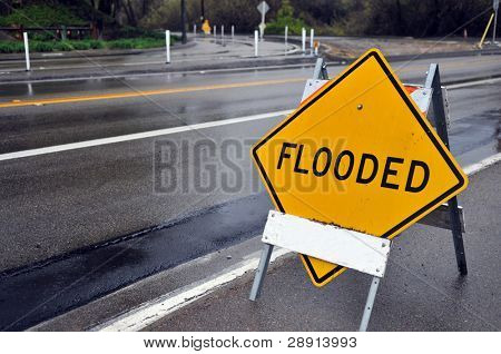 Flooded sign - rainy day themes. Plenty of copy space on left side.