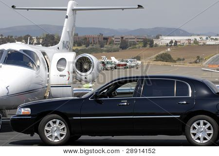 Living the jet-set lifestyle. A limo driver pulls up to an executive jet.