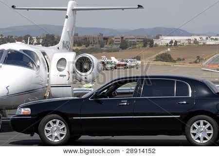 Estilo de vida do jet-set. Um motorista de limusine puxa até um jato executivo.