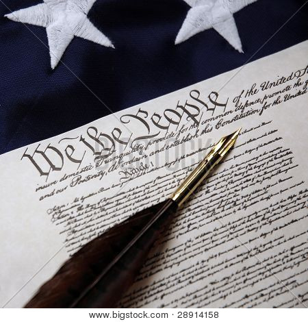 We The People - US Constitution with feather quill pen and original colonial flag.