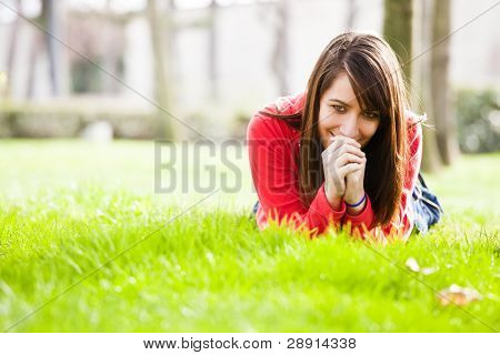 Smiling young woman laying in the grass.