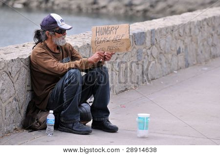 Asking for help - a homeless man panhandles.