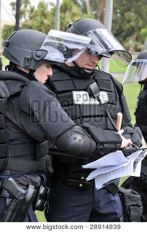 Police officers in riot gear plan their actions