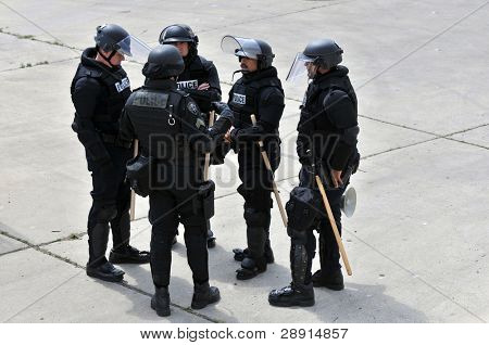 Planning the action - Police in riot gear make plans