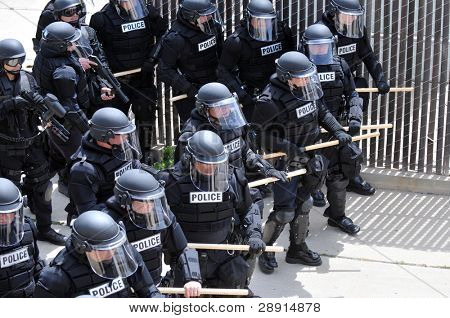 Police officers in riot gear quelling violence.