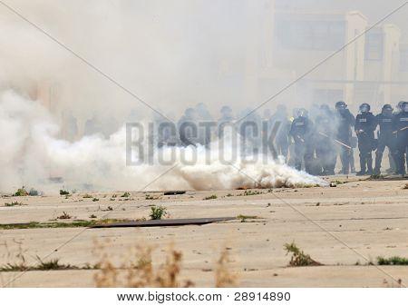 Motim - fumo e policiais em protecao administrar gás lacrimogêneo em uma interferência urbana