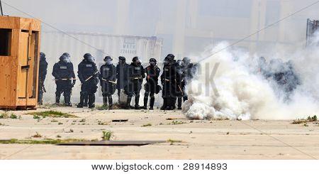 Motim - fumo e policiais em equipamento de proteção em uma interferência urbana