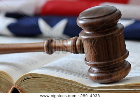 American Justice - gavel over weathered book with flag in background.