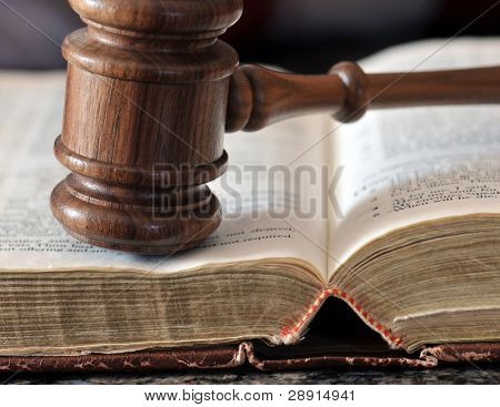 Decision time - gavel over weathered book in a portrayal of judicial system.