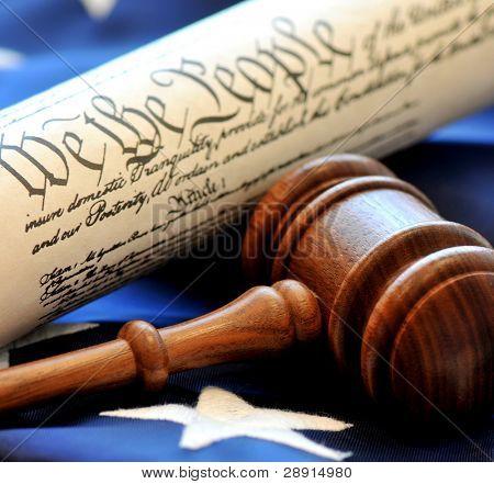 Toma de decisiones legal. Closeup de martillo con la Constitución y la bandera en el fondo.