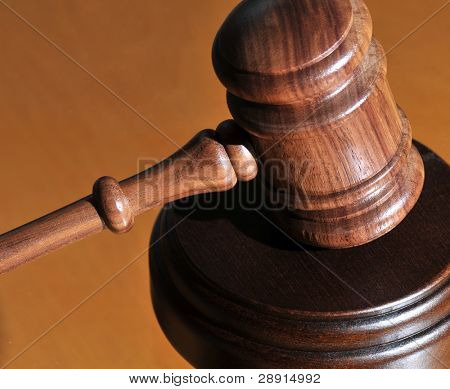Practicing Law - gavel over mustard colored background
