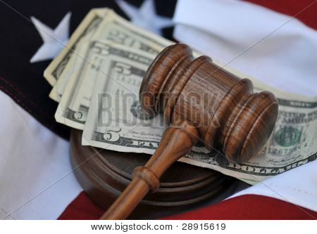 Financial award by a jury or judge - gavel atop money and flag background.