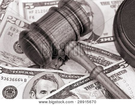 Sepia toned portrayal of financial settlement - wooden gavel atop US currency.