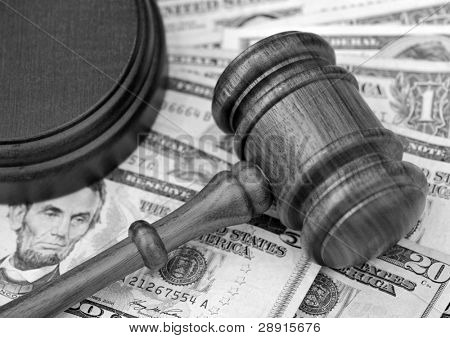 Black and white portrayal of financial settlement - wooden gavel atop US currency.