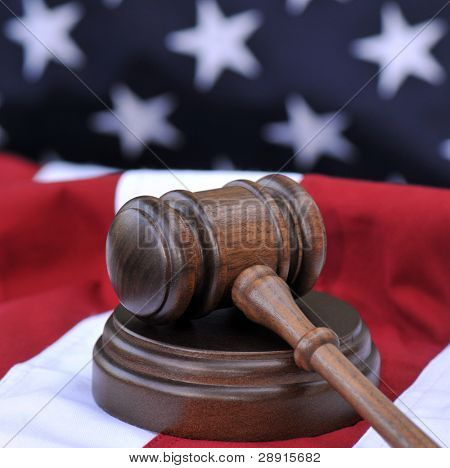 Law of the land - wooden gavel atop a US flag background. Portrayal of the Judicial Branch of government.