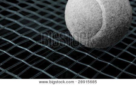 Juego de tenis - ball es blanco y negro, con hilos de colores en tonos azules eléctricos y una profunda blac