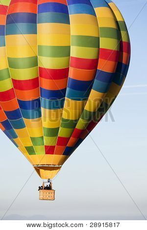 Unrecognizable people traveling in a multicolor balloon