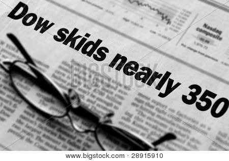 Dow patines casi 130 puntos - gafas encima de diario con titulares desalentador.