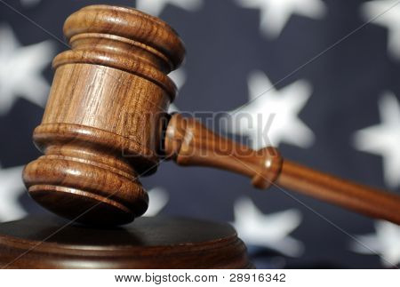 Judges Wooden Gavel with flag in background.