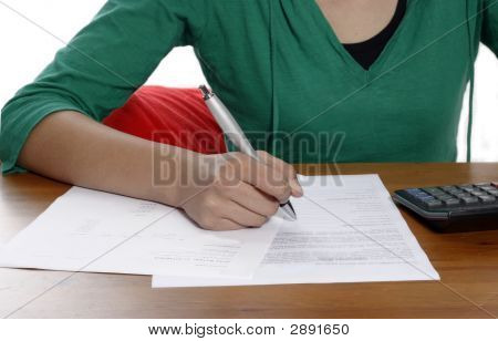 A Young Woman Holding A Pen, Doing Her Taxes