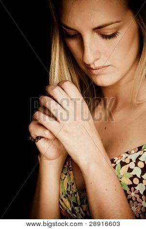 Blond praying woman against black background