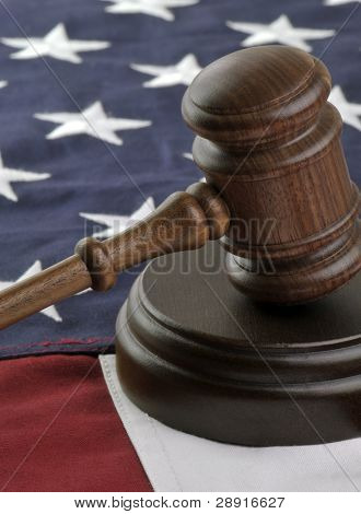 Wooden judge's gavel atop American Flag background.