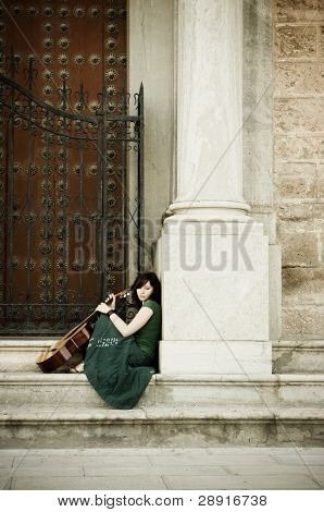 Lone street artist near old church door.