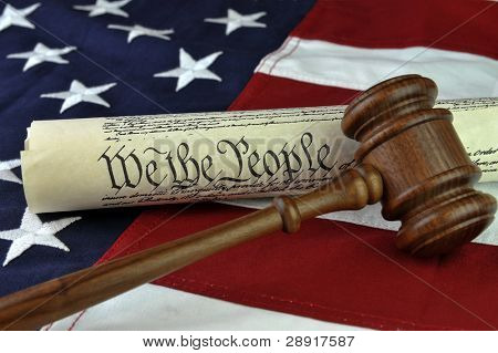 US constitution (We The People document) with wooden judge's gavel over American flag background