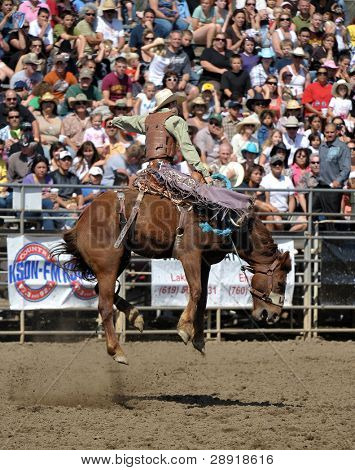 LAKESIDE, CALIFORNIA - APRIL 24: A cowboy on a bucking bronco as the animal jumps straight up at a yearly rodeo event on April 24, 2010 in Lakeside, California.