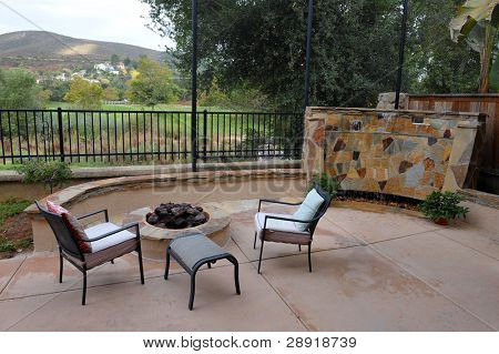 Luxurious backyard of a custom home with firepit and waterfall water-wall on a golf course.