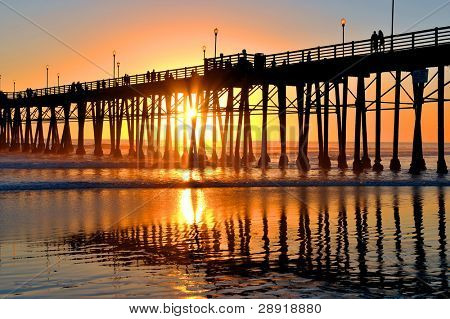 Oceanside Pier at sunset - wooden pier in Southern California with Pacific Ocean in background.