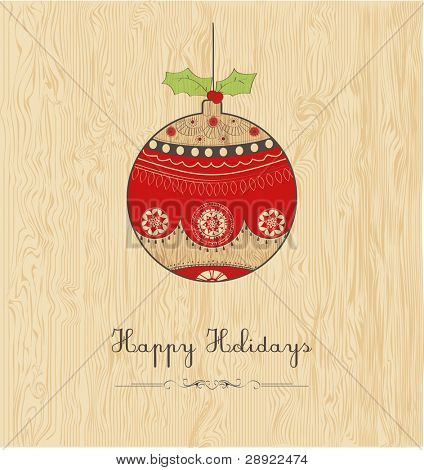 happy holidays; Christmas bauble or ball on wood texture background