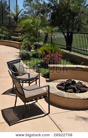 Fabulous backyard on a golf course with a fire-pit, birdbath, hanging plants and flowers