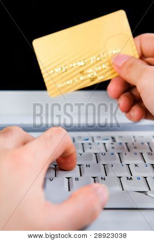 Hand holding the gold credit card while typing on the laptop. All the important information on credit card has been modified.
