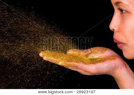 A young woman blow golden glitter from her hands.