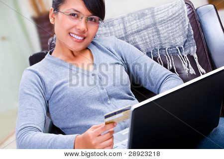 A young woman smiling to camera is about using her gold credit card for online transaction