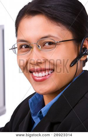 A young beautiful customer service face against the camera with smiling.