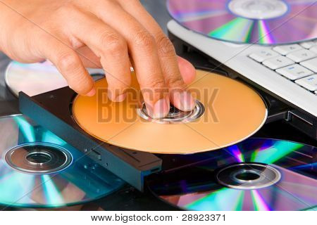Fingers pressing the DVD on DVD-ROM tray of a laptop.
