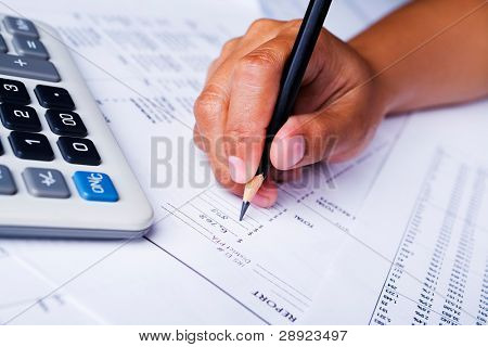 A hand holding a pencil is filling the available space on financial report form.
