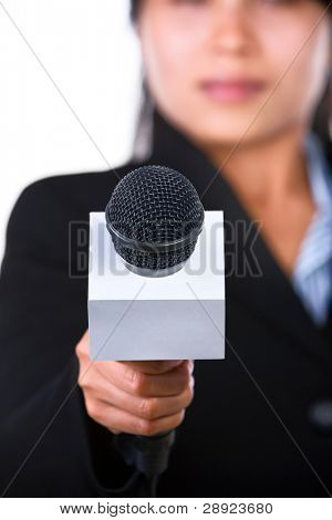 A woman is holding a microphone to the camera. Shot against white background.