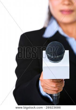 Um host feminino está segurando um microfone apontado diretamente para a câmera. Tiro contra fundo branco.