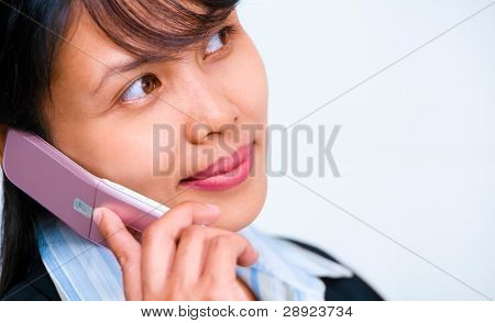 Young businesswoman is listening to her cellphone while looking away at empty space on her right.