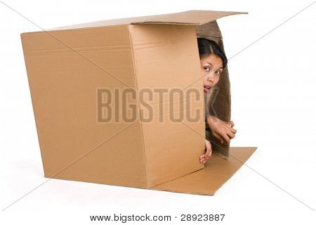 A young woman is hiding inside a box and suspiciously observing around