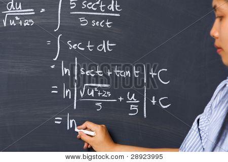 Female student working on mathematics problem on blackboard