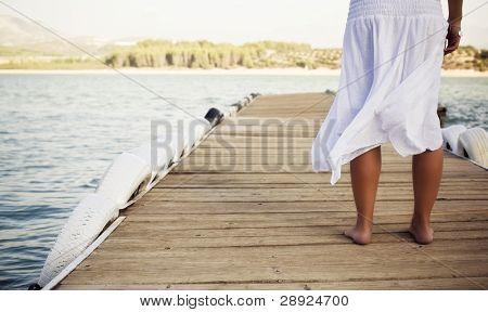 Young shoeless woman on pier .